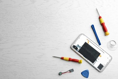 Flat lay composition with broken mobile phone and repair tools on white wooden background. Space for text