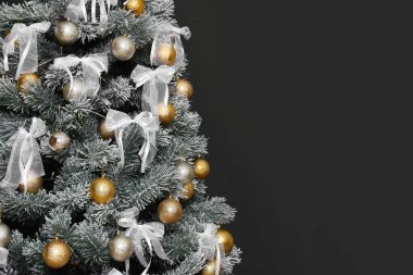 Decorated Christmas tree against black background, closeup