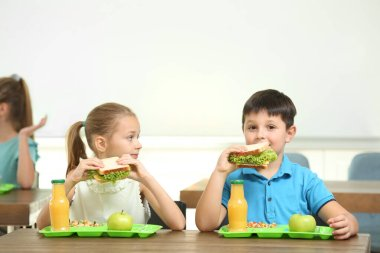 Happy children eating healthy food for lunch in school canteen