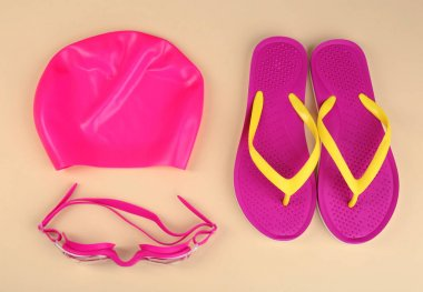 Flat lay composition with swimming accessories on light background
