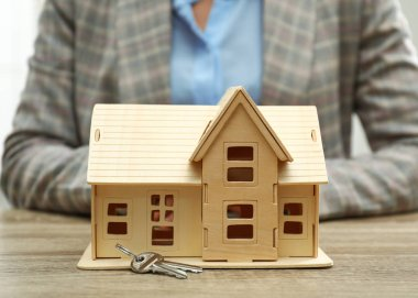 Real estate agent with house model and keys at wooden table, closeup