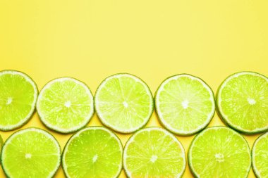 Juicy fresh lime slices on yellow background, flat lay. Space for text