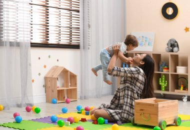 Young nanny playing with cute little baby at home