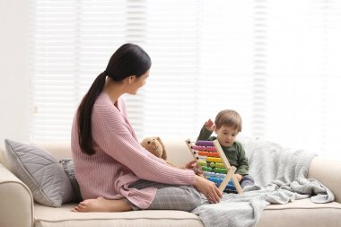 Young nanny and cute little baby playing with abacus at home