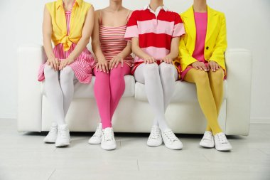 Women wearing colorful tights sitting on sofa indoors, closeup