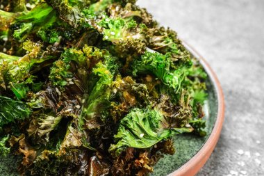 Tasty baked kale chips on grey table, closeup