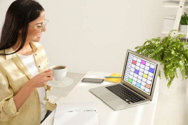 Young woman using calendar app on laptop in office