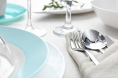 Elegant cutlery with green leaves on table, closeup. Festive set