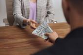 Muž dává úplatek ženy u stolu uvnitř, detailní záběr