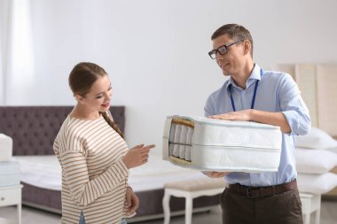 Salesman showing young woman section of mattress in store
