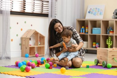 Young nanny and cute little baby playing with toys at home
