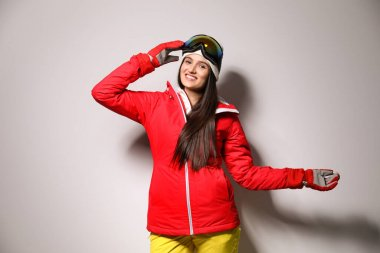 Woman wearing stylish winter sport clothes on light grey background