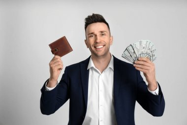 Happy man with cash money and wallet on light grey background