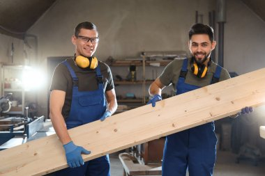 Professional carpenters with large wooden board in workshop