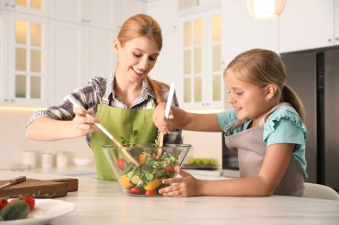 Mother and daughter cooking salad together in kitchen
