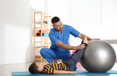 Orthopedist working with little boy in hospital gym