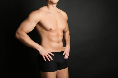 Man with sexy body on black background, closeup. Space for text