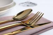Stylish elegant cutlery set with napkin on white table, closeup
