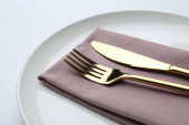 Stylish elegant cutlery with napkin in plate on white background, closeup