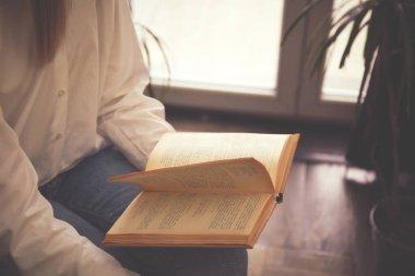 Woman reading book near window indoors, closeup