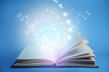 Symphony shining with musical notes from open book on blue background