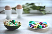 Fotografie small chocolate eggs in colored wrapper on saucer, two eggs in s