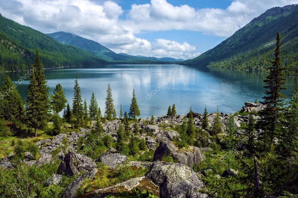 Фотообои Озеро в горах в окружении старых деревьев и больших валунов. Диком труднодоступном месте в горах. Огромные валуны и старые деревья позволяют забыть о цивилизации.