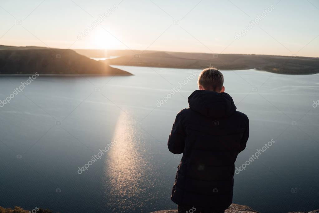 young man on mountain top near calm river
