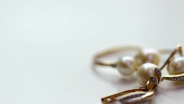 Set gold jewelry from rings and earrings with pearls rotates on the stand