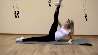 Beautiful young girl in sportswear does exercises on an extension lying