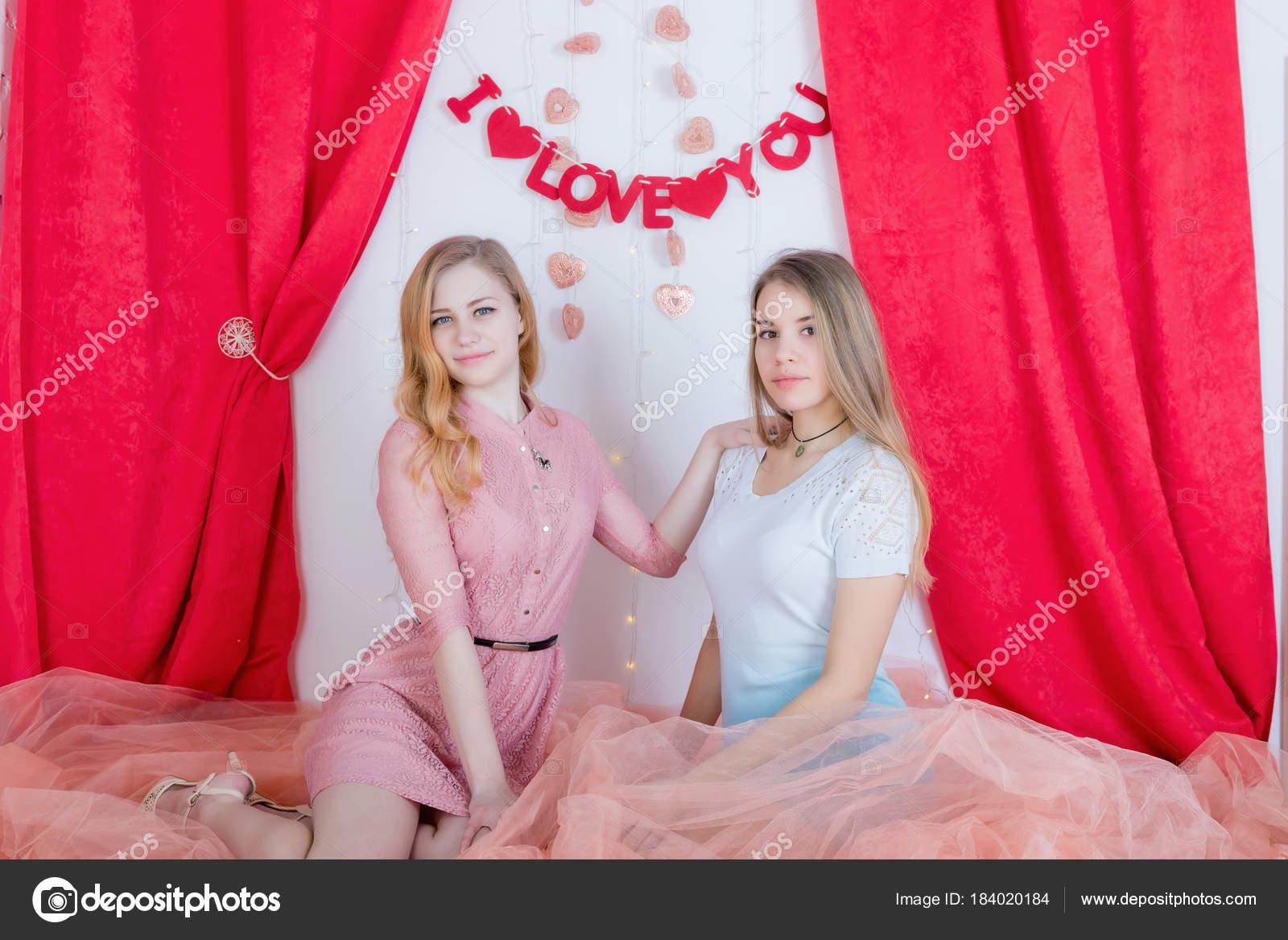 Dos amigas lindas pelo largo en los vestidos sentarse y abrazar otra ...