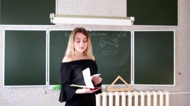 Strict young blonde teacher in black dress scans journal and calls the student to the blackboard for an answer
