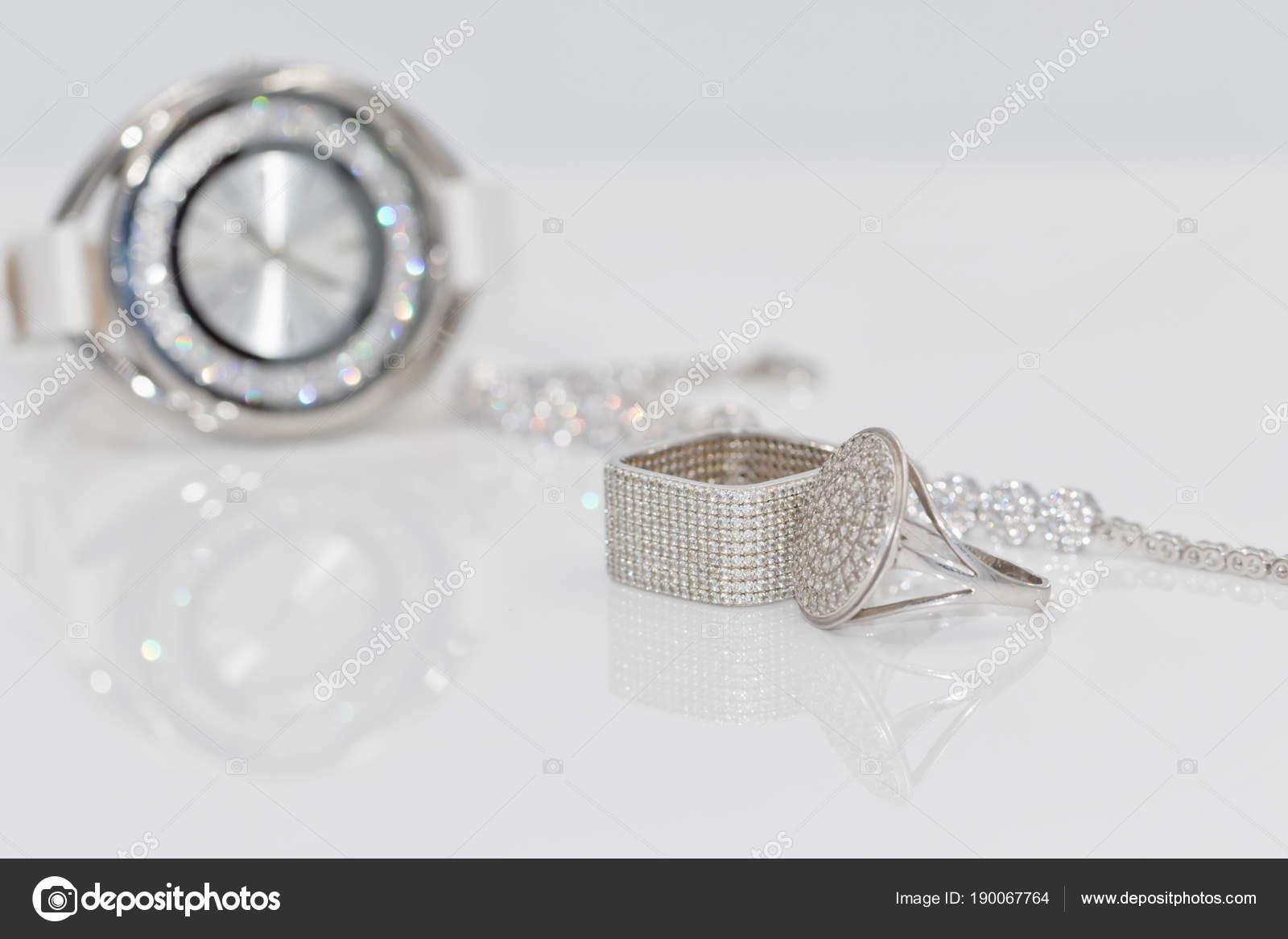 1d397633c97 Ασημένια δαχτυλίδια και σκουλαρίκια στο φόντο των ρολόγια ...