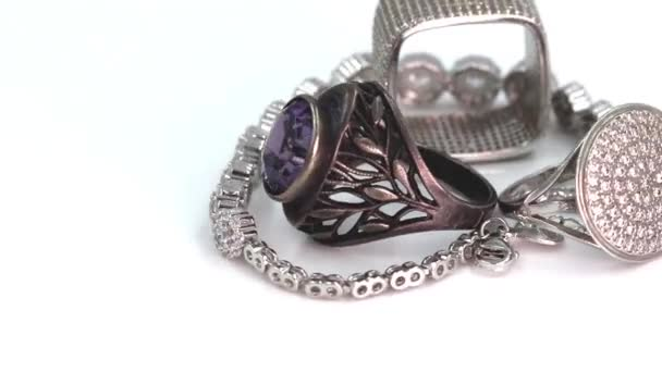 Silver rings of different styles and shapes rotate on a reflective layer around the axis