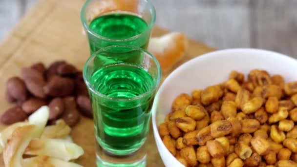 Two shots with green absinthe and different appetizers rotate on a wooden stand