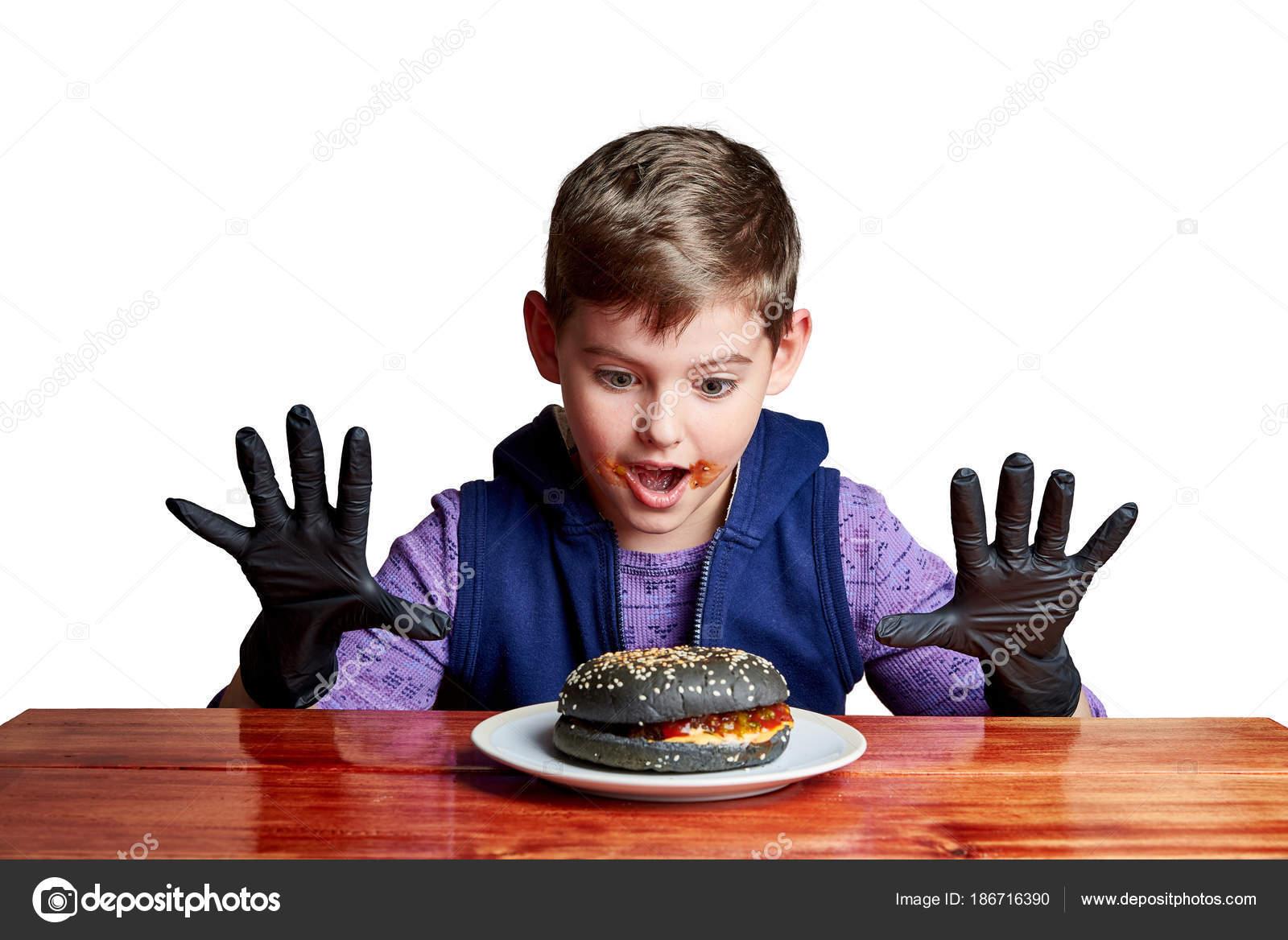 junge schwarze handschuhe emotional einen burger essen tisch auf einem stockfoto. Black Bedroom Furniture Sets. Home Design Ideas