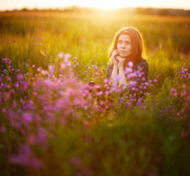A young adult European girl with long fair-haired hair sits on a flowering meadow, holding her hands in front of her face. Pink flowers in the foreground. Beautiful morning light. Square 1:1 sho