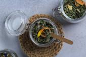 bylinkový čaj ve skleněné nádobě na šedi