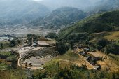 Fotografie agricultural terraces and buildings in beautiful mountains, Sa Pa, Vietnam