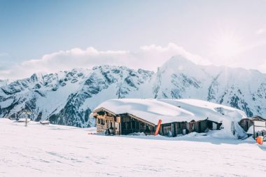 MAYRHOFEN, AUSTRIA - FEBRUARY 19, 2018: traditional wooden cabin at mayrhofen ski resort in beautiful snow-covered mountains, austria stock vector