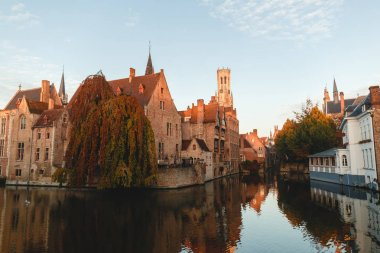 BRUGGE, BELGIUM - NOVEMBER 02, 2016: famous traditional ancient buildings and tower reflected in canal, bruges, belgium stock vector