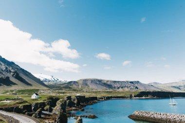 GATKLETTUR, ARNASTAPI, ICELAND - 20 JULY, 2016: beautiful seaside with floating yacht on water, road, rocky mountains and houses on shore in gatklettur, arnarstapi, iceland stock vector