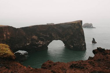 Spectacular view at beautiful cliffs in ocean, vik dyrholaey, reynisfjara beach, iceland stock vector