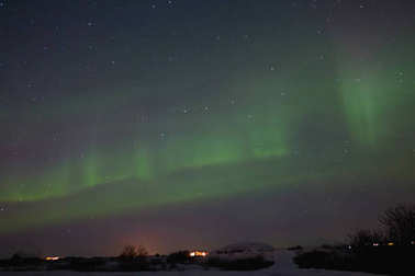 beautiful night view of houses under sky with majestic northern lights in iceland