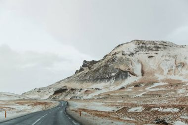empty asphalt road and scenic snow-covered mountains in iceland