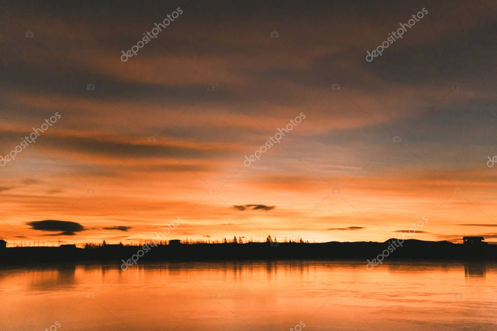 scenic view of skyline with trees and buildings reflected in water at sunset, iceland