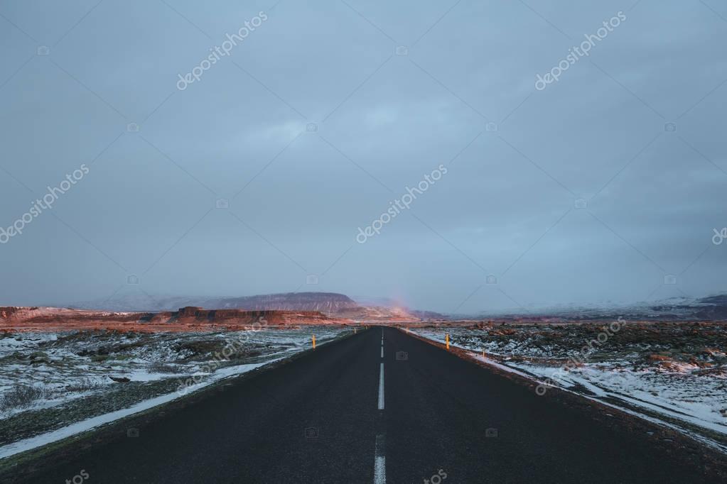 empty asphalt road and snow-covered icelandic landscape at sunrise