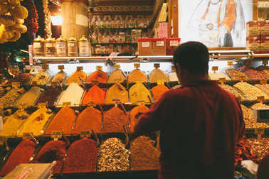 ISTANBUL, TURKEY - OCTOBER 09, 2015: rear view of man choosing spices at market stock vector