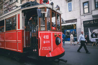 ISTANBUL, TURKEY - OCTOBER 09, 2015: pedestrians and passengers in vintage red tram on street stock vector
