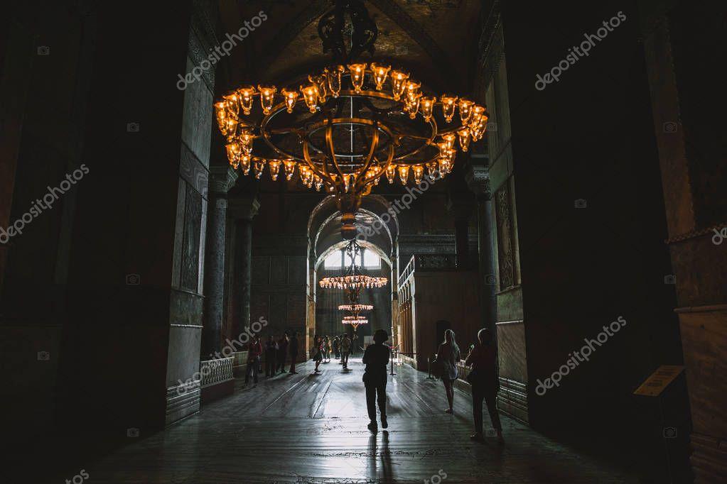 ISTANBUL, TURKEY - OCTOBER 09, 2015: tourists walking under chandelier in suleymaniye mosque